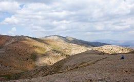 孤立游人在山坐并且反射  库存照片