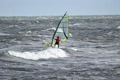 孤立风帆冲浪者在捉住波浪的风雨如磐的海 免版税库存照片