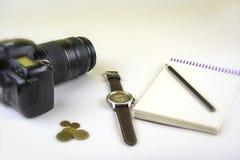 孤立 SLR照相机、硬币、铅笔和笔记薄在白色背景 免版税库存图片
