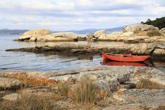 孤零零橙色渔船在岩石停泊了 库存图片