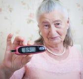 医学、年龄、糖尿病、医疗保健和人概念-有glucometer的资深妇女检查血糖水平的在 免版税图库摄影