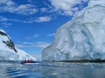 学习一座大冰山的巡航乘客在南极洲 免版税图库摄影