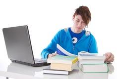 学习与书和膝上型计算机的学生隔绝在白色。 库存图片