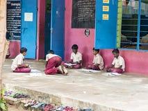 学习与书的小组严肃的儿童朋友男孩同学坐地板室外在学校操场 ?? 免版税库存图片
