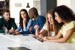 学习与便携式计算机的不同种族的小组青年人 免版税库存图片
