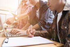 学习与在咖啡馆的计算机的年轻大学生 组 免版税库存图片