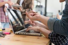 学习与在咖啡馆的计算机的年轻大学生 组 库存照片