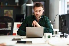 学习与在白色书桌上的便携式计算机的年轻人 库存图片