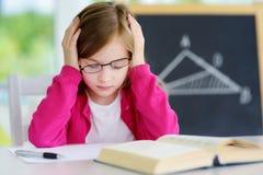学习与堆的被注重的和疲乏的女小学生在她的书桌上的书 免版税库存照片