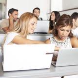 学习与膝上型计算机的学生在教室 免版税库存图片