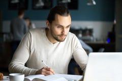 学习与膝上型计算机的被聚焦的男生在咖啡馆 库存照片