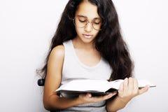 学习与镜片和书的可爱的女孩 免版税图库摄影