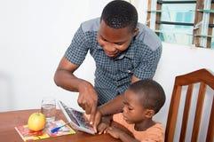 学习与他的家庭老师的男小学生 免版税库存图片