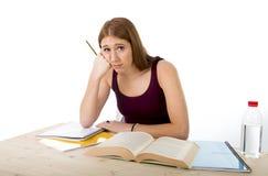 学习为大学检查的大学生女孩在重音感觉疲倦的和试验压力担心 免版税库存照片