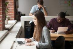 学习为检查的女学生使用膝上型计算机 免版税库存照片