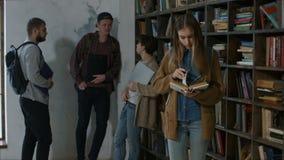 学习为检查的聪明的女学生在图书馆里 股票录像