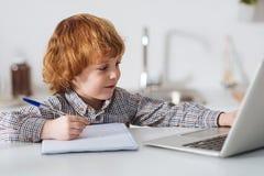 学习为他的测试的坚硬工作的聪明的男孩 免版税库存图片