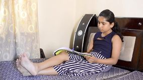 学习书的转动的页印度亚裔女孩孩子,当坐床传播的腿时 股票视频