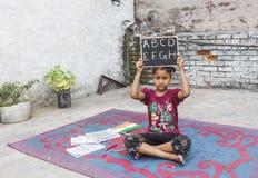 学习初级教育的女孩在开放学校 免版税库存图片