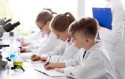 学习化学的孩子在学校实验室 免版税库存图片