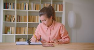 学习和使用片剂的年轻可爱的女生特写镜头画象采取笔记在大学图书馆里 股票录像
