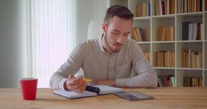 学习和使用片剂的年轻英俊的白种人男生特写镜头画象在大学图书馆里 股票录像