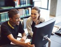 学习在一个现代图书馆里的愉快的年轻学生 免版税库存照片