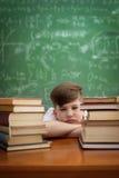 学习在书桌上看起来不耐烦和在与tir的重音下的孩子 库存照片