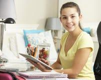 学习在书桌的十几岁的女孩在卧室使用数字式片剂 免版税库存照片