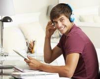 学习在书桌的十几岁的男孩在卧室使用数字式片剂 免版税库存照片