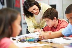 学习在书桌的老师帮助的学生在教室 免版税库存图片