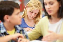 学习在书桌的老师帮助的学生在教室 免版税库存照片