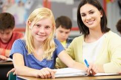 学习在书桌的老师帮助的学生在教室 免版税图库摄影