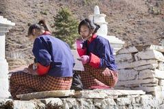 学习在入口前面的两个女孩对Rinpung Dzong 免版税库存照片