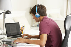 学习在卧室佩带的耳机的书桌的十几岁的男孩 免版税库存照片