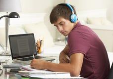 学习在卧室佩带的耳机的书桌的十几岁的男孩 免版税图库摄影