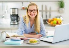 学习在厨房里的微笑的妇女画象 库存照片