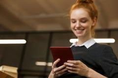 学习在图书馆的愉快的红发十几岁的女孩 免版税库存照片