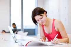 学习在图书馆里的俏丽,年轻大学生 免版税库存图片