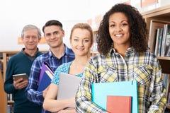 学习在图书馆里的小组成熟学生 免版税库存图片