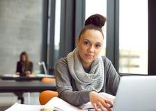 学习在图书馆里的少妇使用膝上型计算机 免版税库存图片