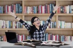学习在图书馆里的快乐的学生 免版税图库摄影