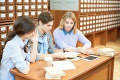 学习在图书馆里的繁忙的学生 免版税库存图片