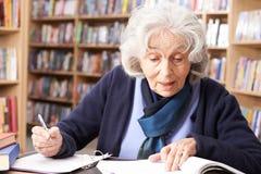 学习在图书馆里的资深妇女 库存图片