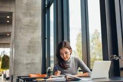 学习在图书馆里的年轻女学生 免版税图库摄影