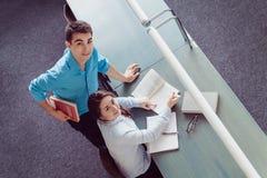 学习在图书馆里的年轻学生 免版税库存照片