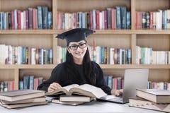 学习在图书馆2里的年轻学士 库存照片