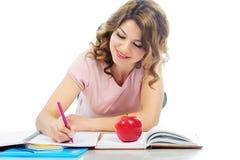 学习在地板上的愉快的女学生隔绝在白色 免版税库存照片