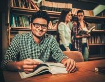 学习在大学图书馆里的多民族小组学生 免版税库存照片