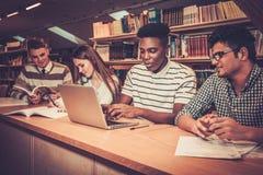 学习在大学图书馆里的多民族小组快乐的学生 库存图片